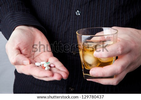 A person holding a glass of alcohol and a handful of pills. - stock photo