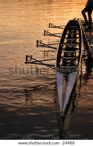 a person holding a row boat along the dock with their foot in the seattle sunrise - stock photo