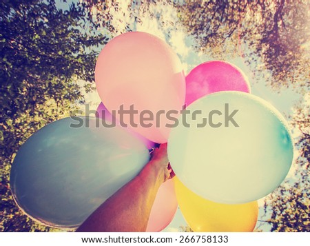 a person holding multi colored balloons toned with a retro vintage instagram filter app or action - stock photo