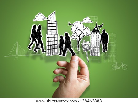 A person holding paper city elements. - stock photo
