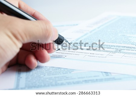 A person is completing the tax form with a pen. - stock photo