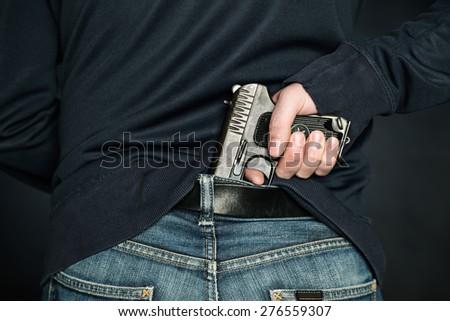 A person is hiding a handgun under the denim belt. - stock photo