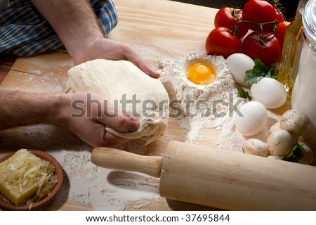 A person kneading dough on wooden table - stock photo