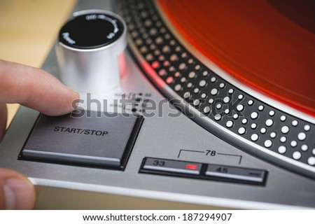 a person pressing the stop button of a record player - stock photo