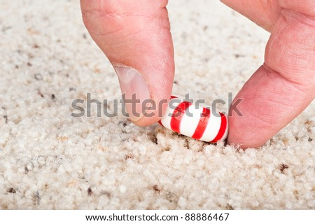 A person pulling a sticky candy mint off the carpet. - stock photo
