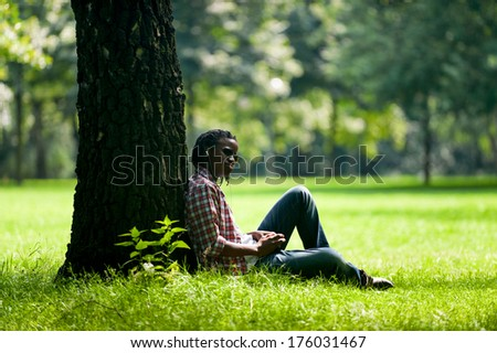 A person sitting against a tree on the grass. - stock photo