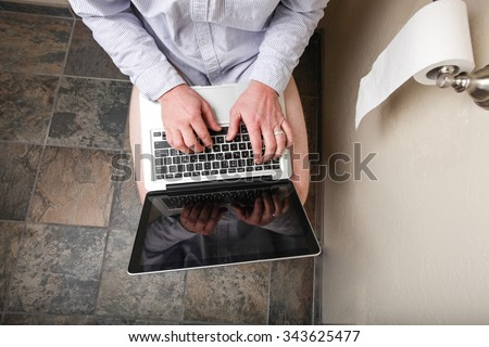 A person using their computer while on the loo - stock photo