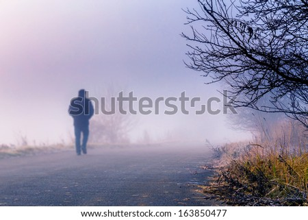 A person walk into the misty foggy road in a dramatic sunrise scene with abstract colors - stock photo