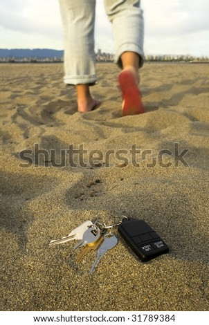A person walks away, leaving their keys in the sand at the beach. - stock photo