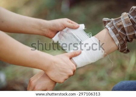 A person wrapping his friends injured arm in gauze - stock photo