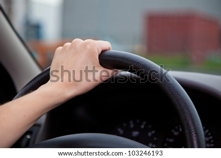 A persons hand holding steering wheel of a car. - stock photo