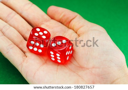 A persons hand with two translucent red dice with white numbers on them showing the numbers the person wishes roll, five and three. - stock photo
