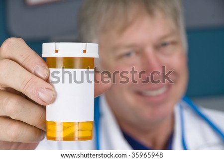 A pharmacist doctor holds up a pill bottle. Label is left blank for copy. - stock photo