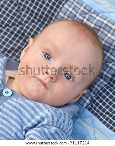 A photo of a beautiful baby boy on a blue carpet - stock photo