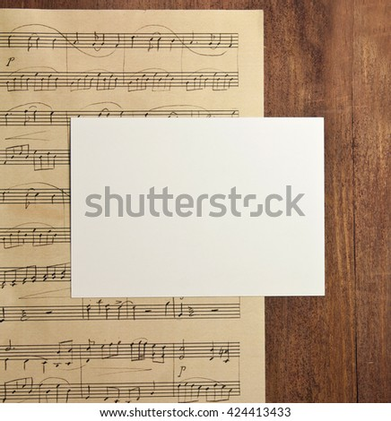 A photo of a blank white post card with copyspace, on a piece of aged sheet music (piano concert), on a dark wooden background texture, shot from above; an invitation template - stock photo