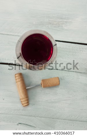 A photo of a glass of red wine with an old wooden corkscrew with a cork, shot from above on a teal blue wooden background texture with copyspace - stock photo