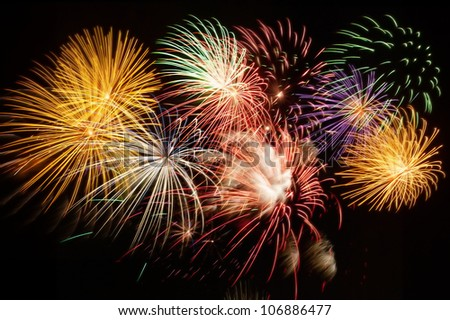 A photo of a large display of fireworks in night sky - stock photo
