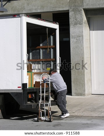 A photo of a man unloading a truck - stock photo