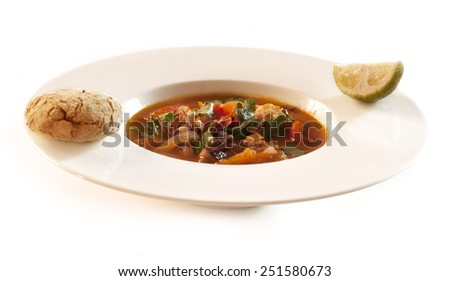 A photo of a plate of homemade tomato and seafood soup, garnished with coriander leaves, with a bun and a lime slice - stock photo