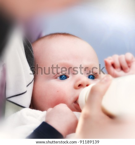 A photo of a small baby boy drinking milk - stock photo
