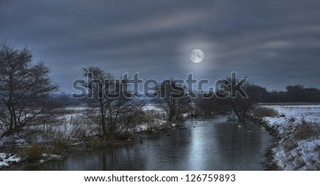 A photo of a small river in winter landscape - moon shining - stock photo