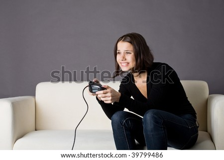 A photo of a young woman playing video games - stock photo