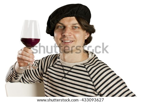 A photo of an attractive smiling Frenchman in traditional clothes (a beret and a striped sweater), with a glass of red wine, on white background - stock photo