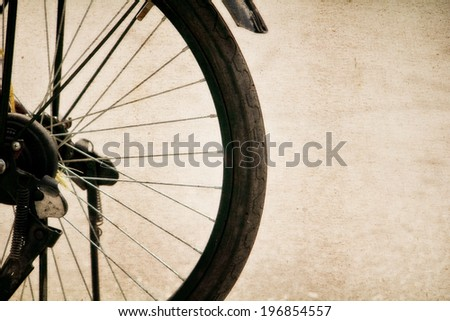a photo of close up old-fashioned bicycle  wheel side walk way - stock photo