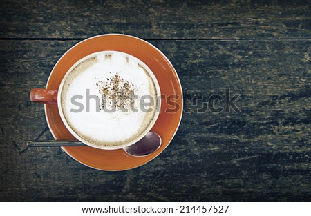 a photo of coffee in cup on wood table - stock photo