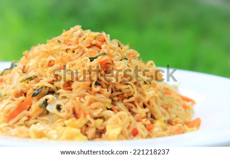 a photo of instant noodle pan fried on white dish,green natural background - stock photo