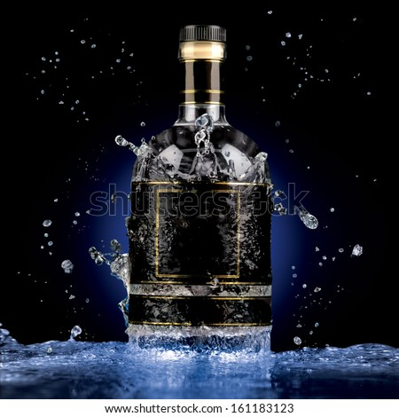A photo of luxury alcohol bottle in water splash. - stock photo