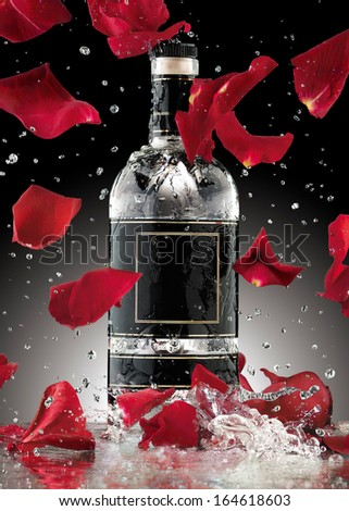 A photo of luxury alcohol bottle with falling rose leaves. - stock photo