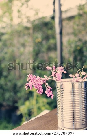a photo of  pink flowers in can,garden view - stock photo