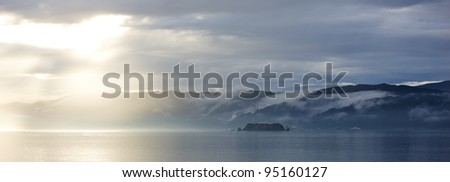 A photo of ship, Sunset, ocean and mountains - stock photo