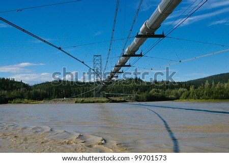 A photo of the Alaskan Oil Pipeline crossing over a river. - stock photo