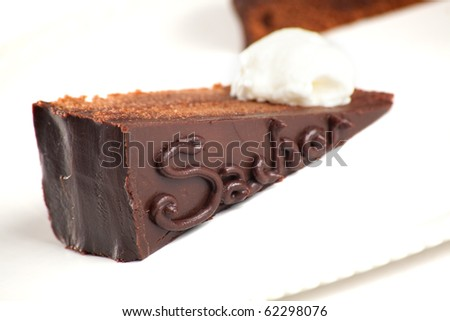 A photo of the Austrian Sacher Torte cake, filled with apricot preserve and frosted with darl chocolate with a dollop of whipped cream. Isolated on white - stock photo