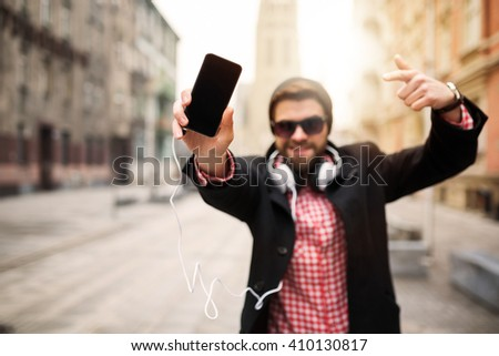 A photo of young, trendy man bragging about his mobile - stock photo