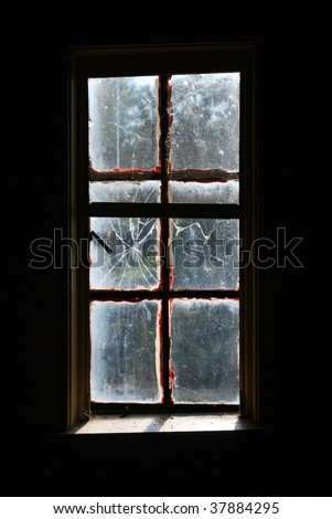 A photograph looking out of a dark broken glass window into the outside light. - stock photo