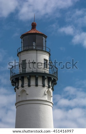 A photograph of a beautiful tall Lake Michigan lighthouse against a pleasant summer sky. - stock photo
