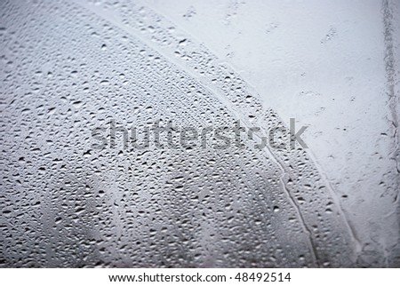A photograph of rain drops on a vehicles front windshield. - stock photo