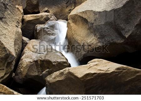 A photograph of water streaming down rocks at Yosemite Falls in Yosemite National Park. - stock photo
