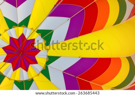 A photograph taken from inside a hot air balloon shows the vibrant colors and patterns of its design. - stock photo