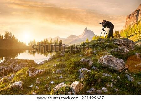 A photographer in the beautiful lake Federa - stock photo