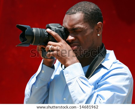 a photographer prepares to take a photo with his digital camera - stock photo