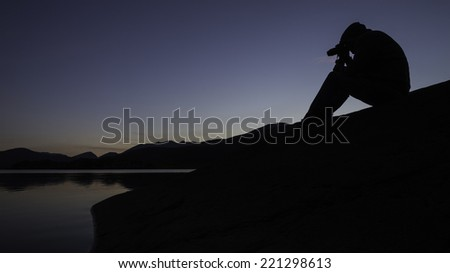 A photographer, sitting on a rock, shoots a lake at dusk.  - stock photo