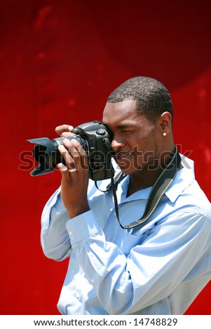 a photographer takes a photo with his digital camera - stock photo