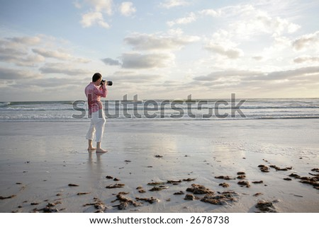 A photographer taking a photo on the beach. - stock photo