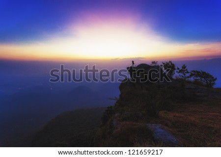 A photographers takes pictures from the top of mountain - stock photo