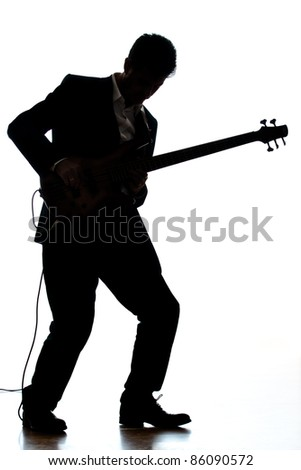 A photographic silhouette of a Bass Guitar Player - stock photo