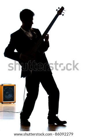 A photographic silhouette of a Bass Guitar Player with an electric amplifier - stock photo